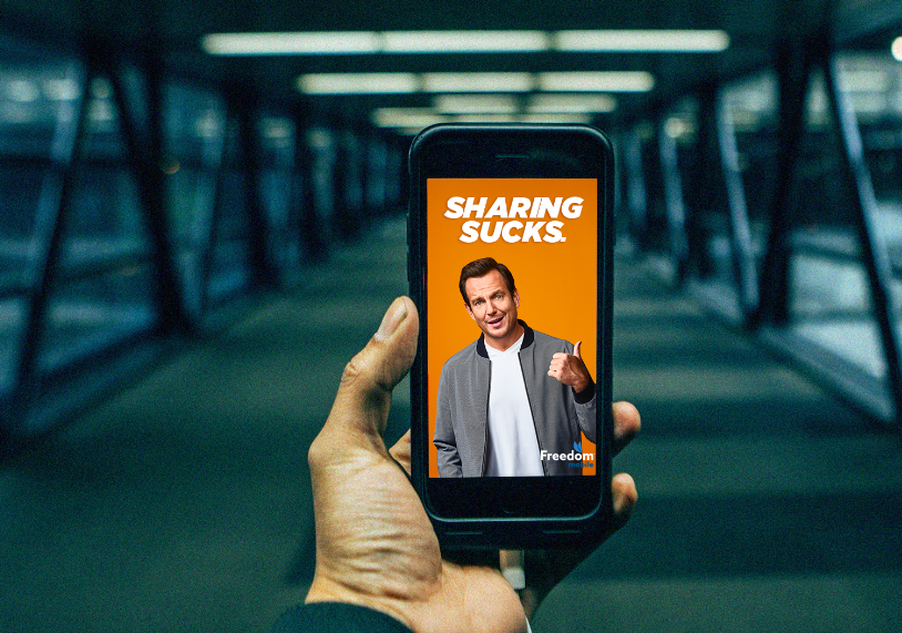 a hand holding a mobile phone showing Freedom Mobile's spokesperson, Will Arnett